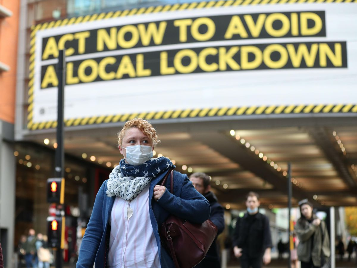 A woman wearing a mask under an 'Act now to avoid a local lockdown' notice