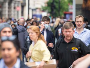 A man wearing a face mask among a crowd of pedestrians on Oxford Street, London.