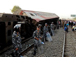 Security forces stand guard as people gather at the site where a passenger train derailed near Banha, Qalyubia province, Egypt (Tarek Wagih/AP)