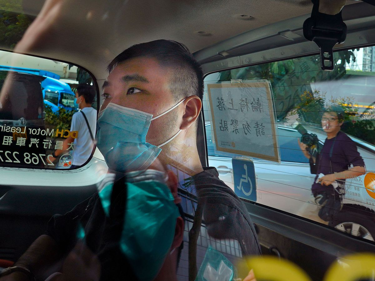 In this July 6, 2020, file photo, Tong Ying-kit arrives at a court in a police van in Hong Kong