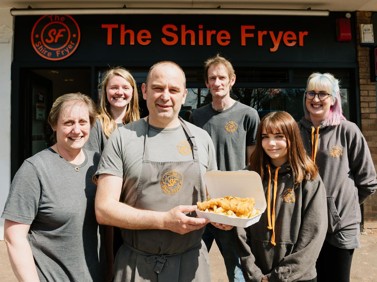 Paul Kayiatou owner of The Shire Fryer, celebrates with staff after being voted among the country's best chip shops