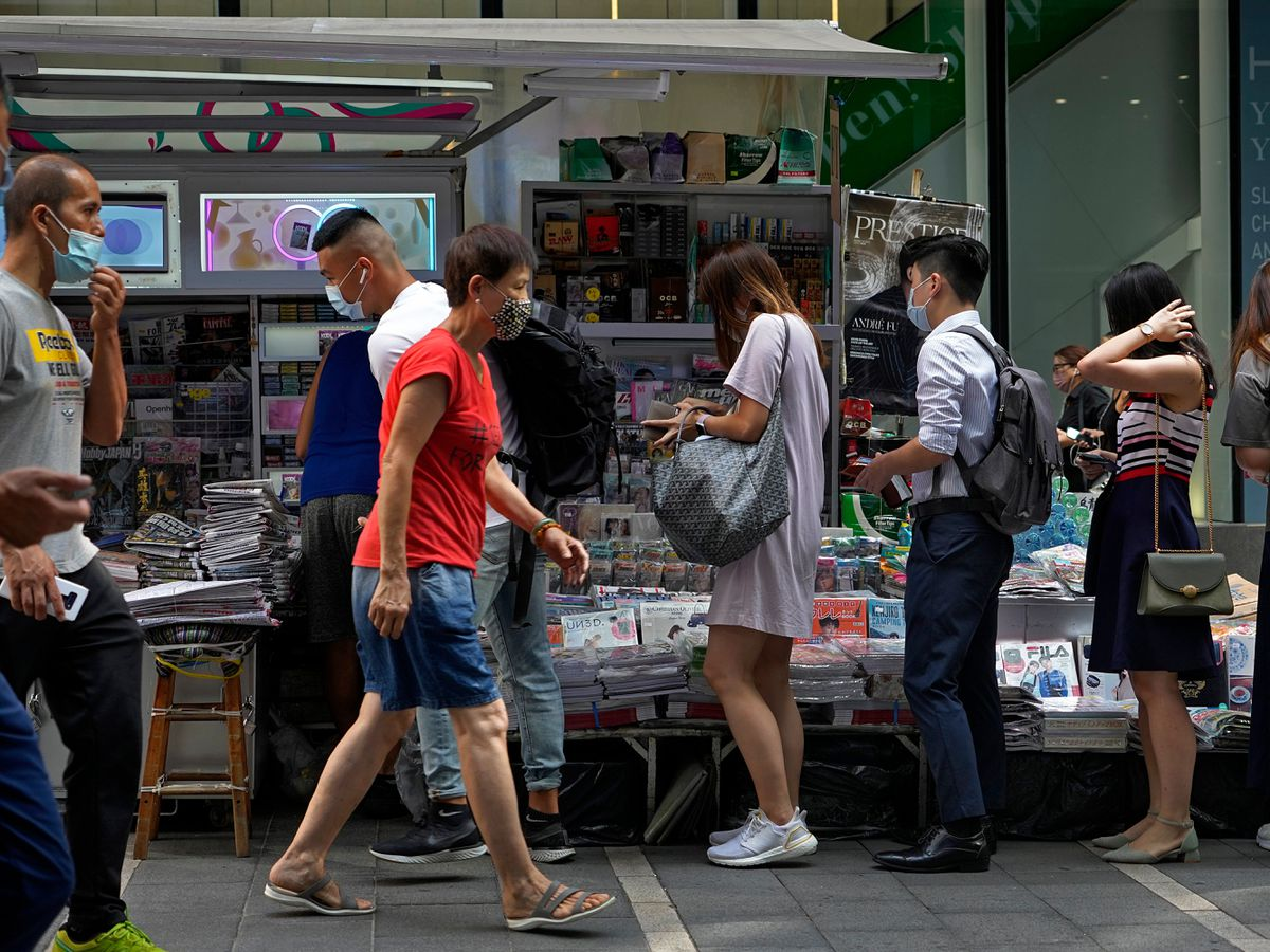 People queue up to buy Apple Daily at a downtown street in Hong Kong on Friday