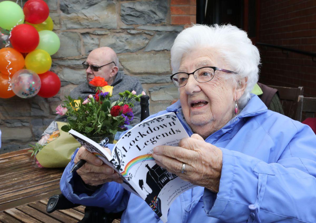 Ena Strange 99  enjoying reading  a copy of the book
