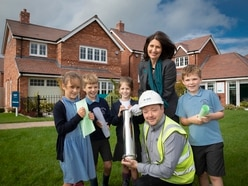 Schoolchildren bury time capsule at housing development near Market Drayton