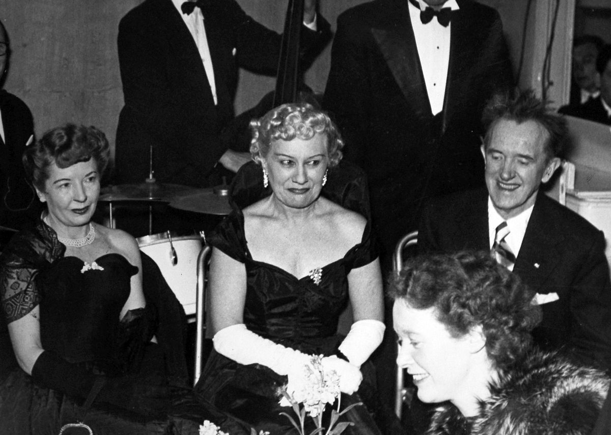 Stan Laurel at an unidentified reception in Shrewsbury in April 1952, with his blonde wife – who became a crime victim – and, left, Oliver Hardy's wife.