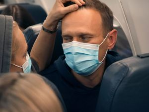 Alexei Navalny and his wife Yulia sit on the plane on a flight to Moscow