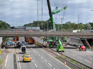 The scene showing the crane and bridge beams at Junction 10 of the M6