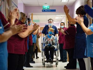 Margaret Keenan, 90, is applauded by staff as she returns to her ward after becoming the first person in the United Kingdom to receive the Pfizer/BioNtech Covid-19 vaccine