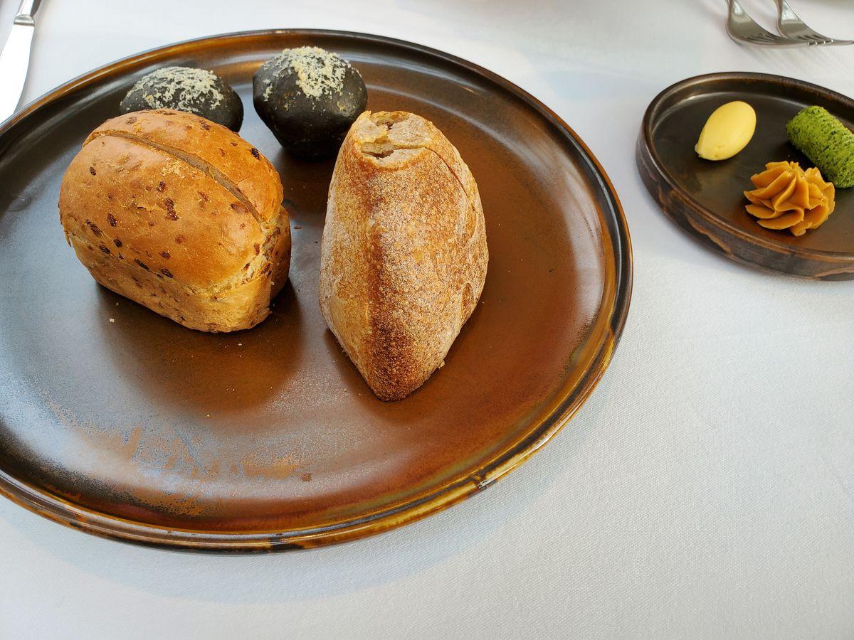Una selección de pan servido con tres mantequillas