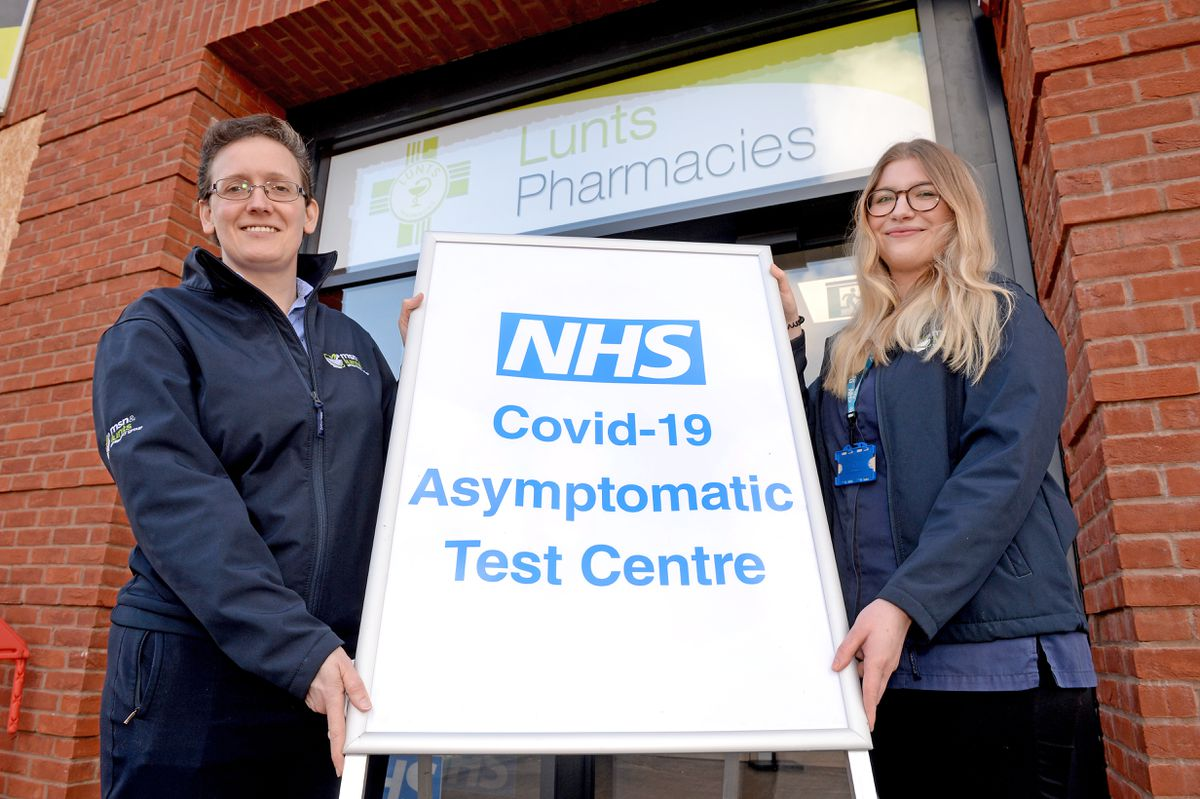 Helen Grass and Chelsie Matthews advertise the rapid tests on offer at pharmacies