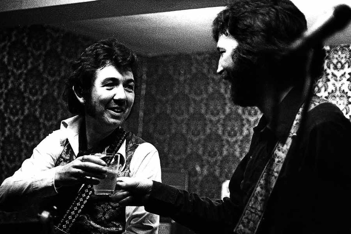 Ronnie Lane and Eric Clapton share a tot