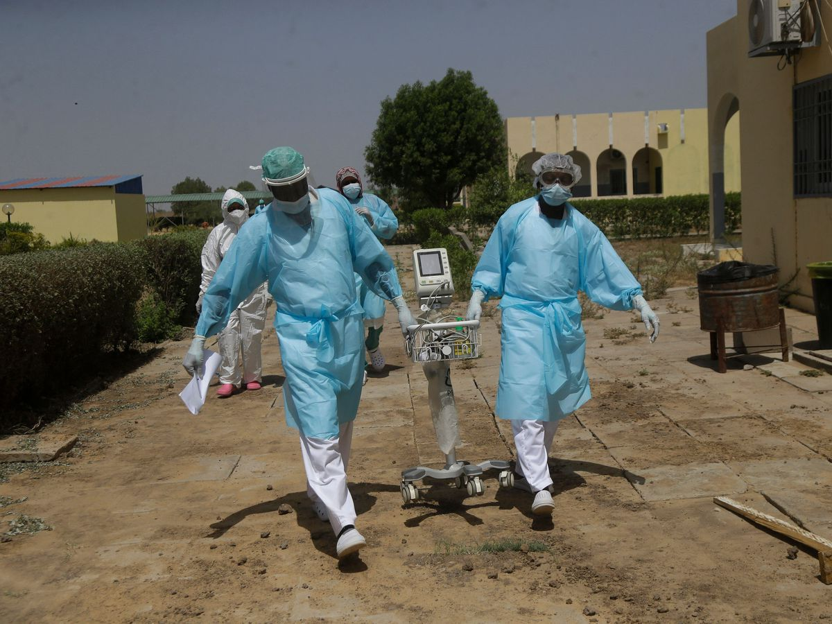 Doctors caring for Covid-19 patients in Chad carry medical equipment