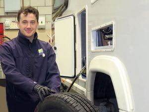 Service engineer Tom Hancock checks the tread on a touring caravan tyre during a service in Salop Leisure's workshops
