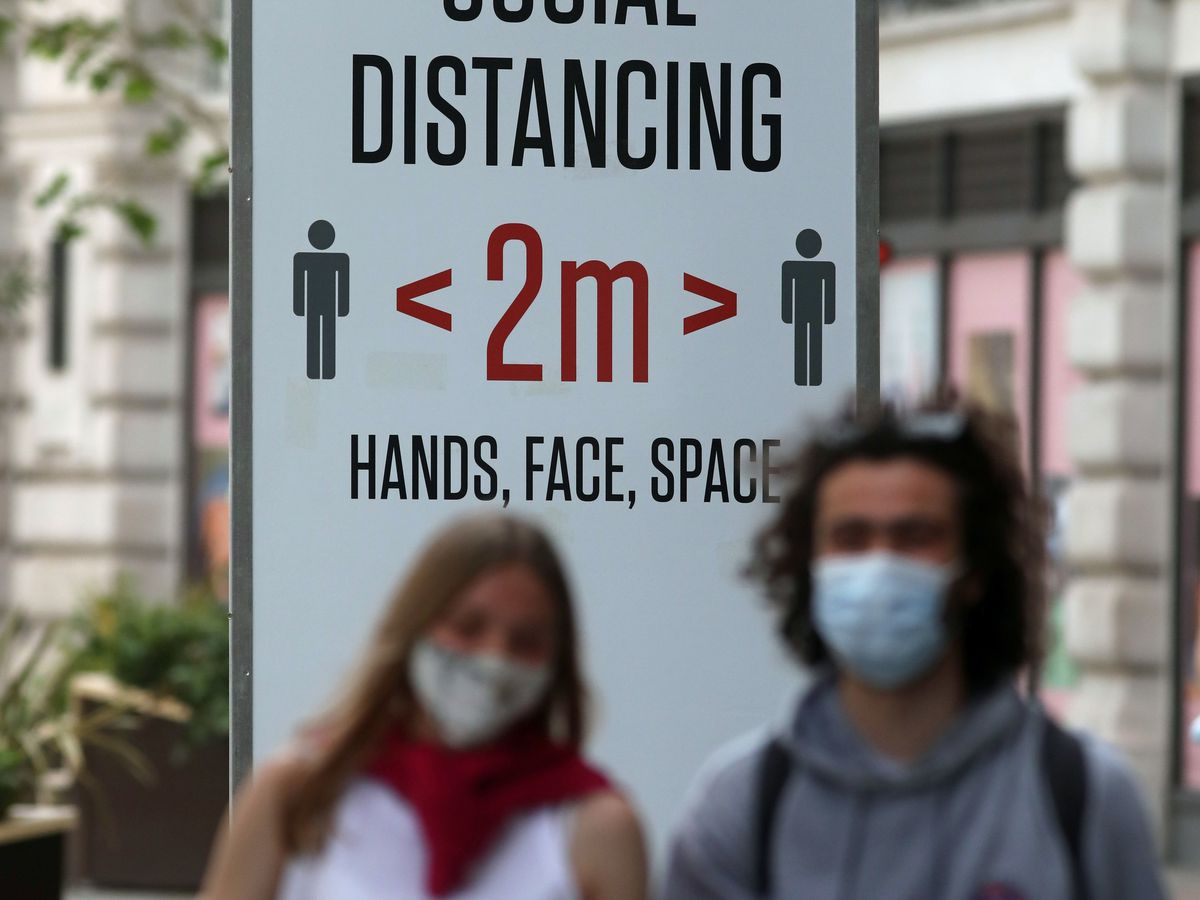 People in the street near a sign offering public health advice during the coronavirus pandemic