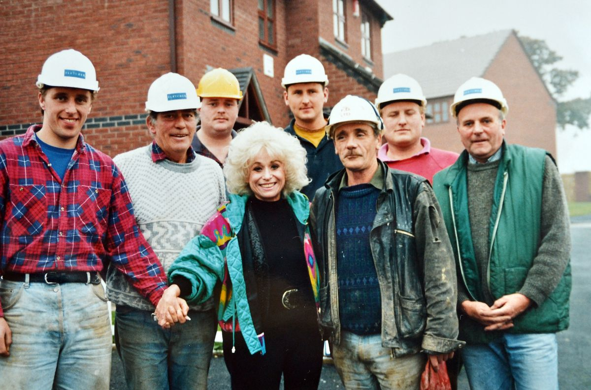 "Members of the Fletcher Homes workforce got a ""carry on building"" message from screen star Barbara Windsor when she launched the firm's affordable rural homes scheme at Berrington Green, near Shrewsbury, back in January 1994. Barbara was best known at the time for  the Carry On films but soon forged a new career in EastEnders. Unfortunately we have no names for the workers seen with her."