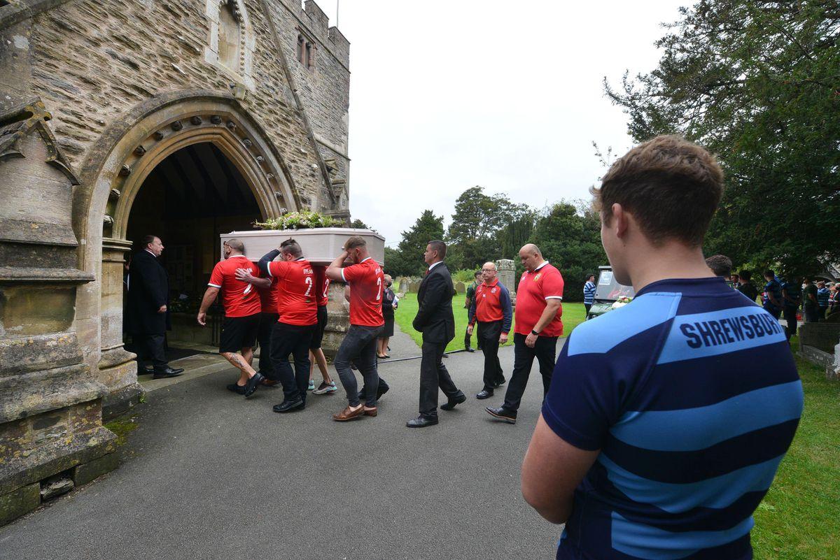 Pallbearers enter the church