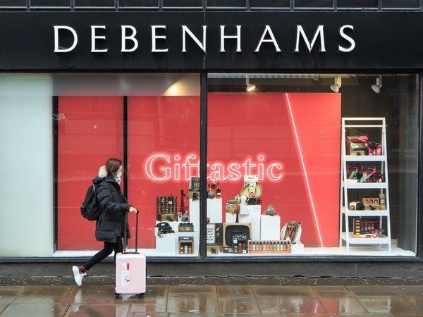 A woman walks past a Debenhams store
