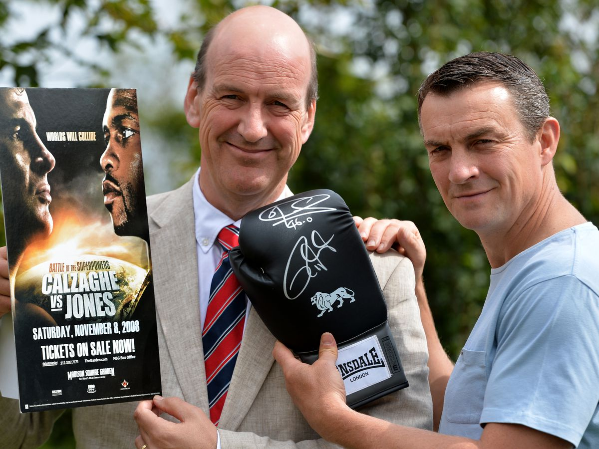 Richie Woodhall, right, and Jeremy Lamond of Halls get ready to auction off the glove signed by boxing legends Joe Calzaghe and Roy Jones Junior