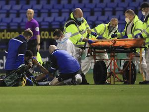 Scott Golbourne of Shrewsbury Town receives treatment on the pitch for an injury.