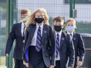 Pupils wear protective face masks as they walk to school