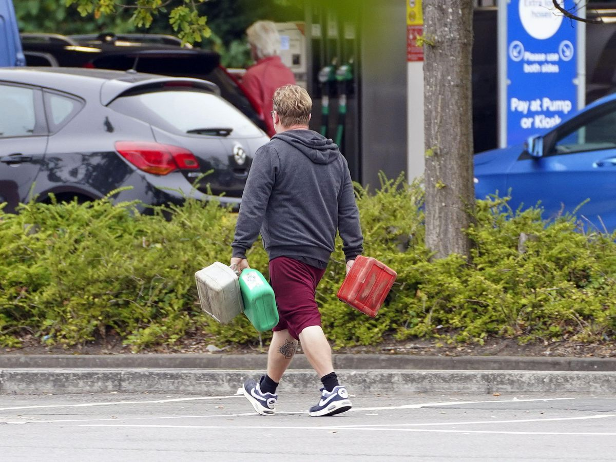 A man carrying containers to a filling station